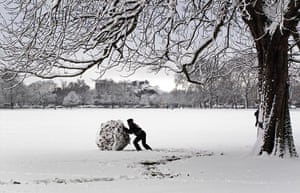 Snow: man pushes a giant snow ball