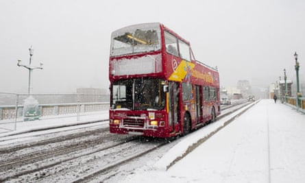 A sightseeing tour bus on Southwark bridge, London in a snowstorm.