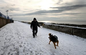 Cold weather continues: Collin Woods and his dog Zeb take a snowy walk on Porthcawl seafront