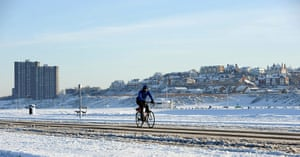 Cold weather continues: A man cycles along a snow-covered road in New Brighton near Liverpool