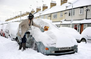 Cold weather continues: A woman clears deep snow from her car on a street in Cirencester, Wiltshire