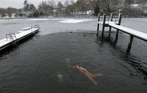 Cold weather continues: A man swims in the partially frozen men's pond at Hampstead Heath