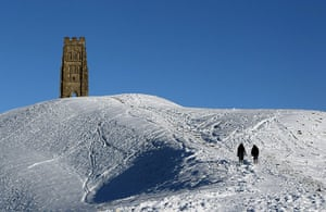 Cold weather continues:  A couple walk in the snow below Glastonbury Tor in Somerset