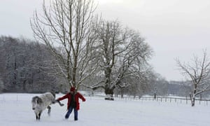 A horse kicks at a woman in a snow-covered field in Helperby, north England.