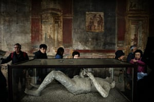 24 hours in pictures: Tourists look at a body cast at archeological site of Pompeii
