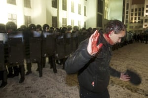 Belarus election violence: A bleeding opposition supporter walks in front of riot police
