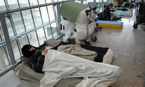 Passengers rest at terminal five at Heathrow airport