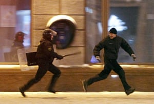 Belarus election violence: A riot policeman chases an opposition protester during a rally