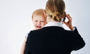 Businesswoman on her mobile phone carrying a baby