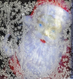 snow continues in uk: A toy Santa Claus