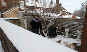 Police officers search the garden of a house in Stoke-on-Tren