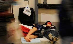 Airline passengers sleep on the floor of Heathrow airport