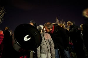 Lunar Eclipse: On a Reykjavik parking lot people gather around a telescope