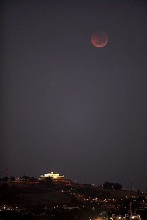Lunar Eclipse: A total lunar eclipse is seen as the full moon is shadowed by the Earth