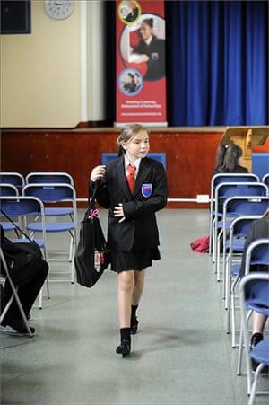 School Uniforms: A schoolgirl walks through an assembly hall in smart uniform