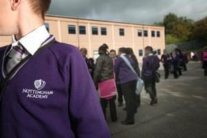 School Uniforms: Children in smart uniform stand casually in a playground