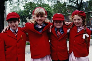 School Uniforms: Four young children show their bright red traditional uniform