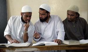Muslim students discuss before the start of their class at Islamic madrassah Jamia Binori in Karachi