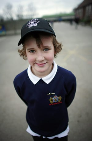School Uniforms: A young boy stands proudly in his casual uniform with cap