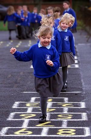 School Uniforms: Girls in bright blue school uniform play hopscotch