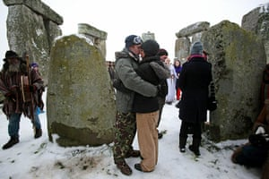 Winter Solstice: A couple kiss and embrace at a sunrise service at Stonehenge