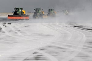 Travel Chaos: Airport workers clear snow from the second runway at Manchester Airport
