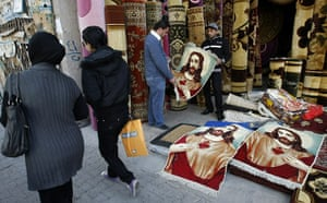 Christian in Middle East: Iraqi women walk past a carpet shop with a portrait of Jesus Christ
