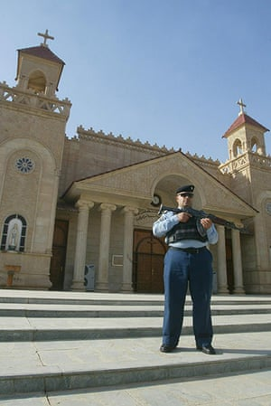 Christian in Middle East: An Iraqi policeman stands guard outside a church in Kirkuk