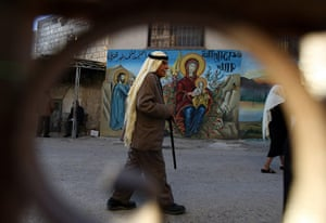 Christian in Middle East: A Palestinian man walks past Christian murals in West Bank