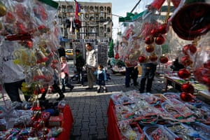 Christian in Middle East: People walk past a street vendor selling Christmas decorations. Iraq