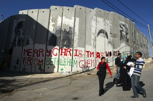 Christian in Middle East: Palestinians walk past a Christmas greeting painted on separation barrier