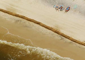 2010: year in pictures: Sunbathers behind wall of haybales absorbing oil from Gulf of Mexico spill