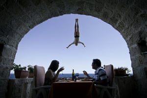 2010: year in pictures: Lunchers watch a cliff-diver in Polignano a Mare, Italy