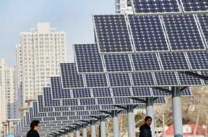 2010 green technologies: Residents walk pass a group of solar panels in Shenyang