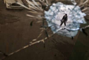 24 hours : Kabul, Afghanistan: A security guard is seen through a bullet hole
