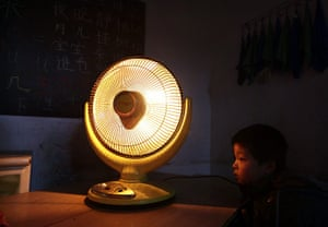24 hours : Beijing, China: A boy sits next to an electric heating fan in a classroom