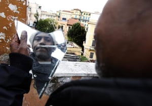 24 hours : Rome, Italy: A Somalian refugee trims his moustache at the former embassy