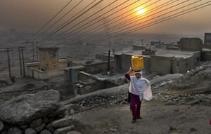 24 hours : Kabul, Afghanistan: An Afghan girl carries water in a plastic container
