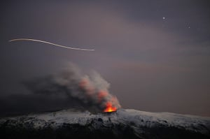 Year in business: The path of a plane is seen over the erupting volcano near Eyjafjallajokull
