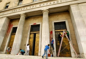 Year in business: Workers clean the main entrance of the Bank of Greece in Athens