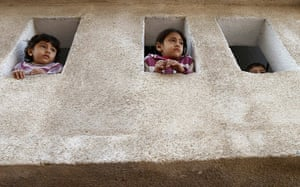 24 hours in pictures: Palestinian children peek from windows to follow the funeral procession