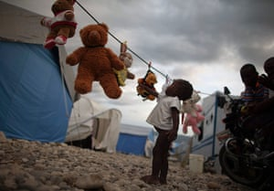 24 hours in pictures: A child reaches out for a stuffed animal hanging to dry at Caradeux Camp