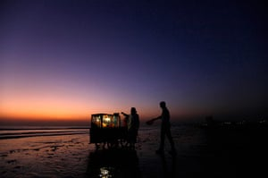 24 hours in pictures: A beach-goer goes to collect gol gappa from a vendor