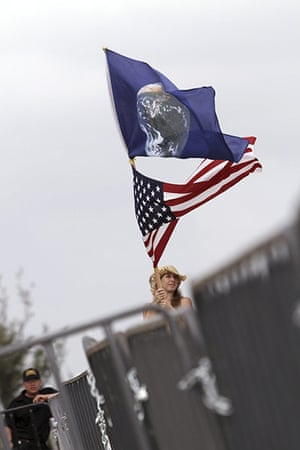 Week in Cancun COP16: A woman waves a U.S. flag and a flag showing the earth  in Cancun