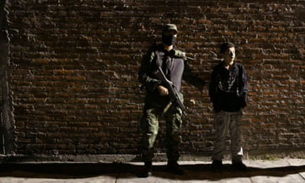 A soldier stands with the teenage suspect, known as El Ponchis, in Cuernavaca, Mexico