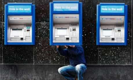 A man repairs a cash machine outside a bank in London