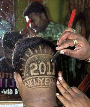 New Year Celebrations: Karad, India: A man has his head shaved