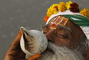 New Year Celebrations: Allahabad, India: A Hindu holy man, blows a conch shell 2011