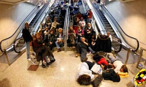 Stranded passengers rest at Madrid's Barajas airport after flights were cancelled due to a strike