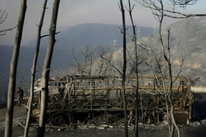 24 Hours: An Israeli soldier stands next to a bus which was caught in the wildfire